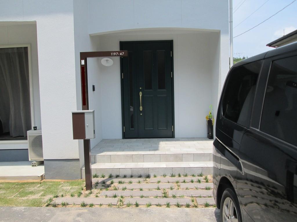 門柱は人気のCHABA、アプローチにはレイルスリーパー、タマリュウを使用で お家の白い外壁とグリーンのドアが映える玄関周りになりました